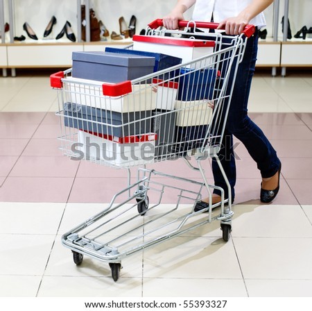 Woman pushing a shopping cart full of shoe boxes in a shoe store. Lower half body view.