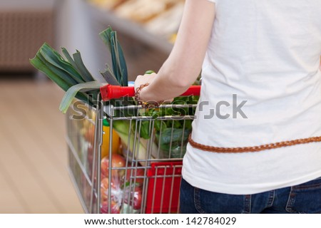 Woman pushing a shopping trolley filled with fresh fruit and vegetables for a healthy diet, closeup view - stock photo