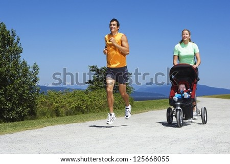 woman pushing a stroller with baby walking beside a man jogging, with bushes and trees in the background - stock photo