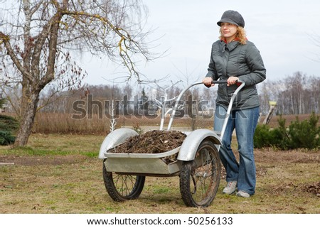 Woman pushing barrow in garden, early spring scene - stock photo