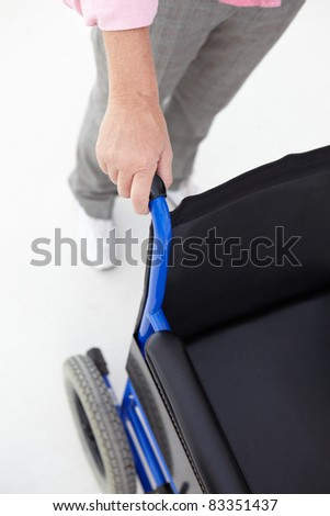 Woman pushing empty wheelchair - stock photo