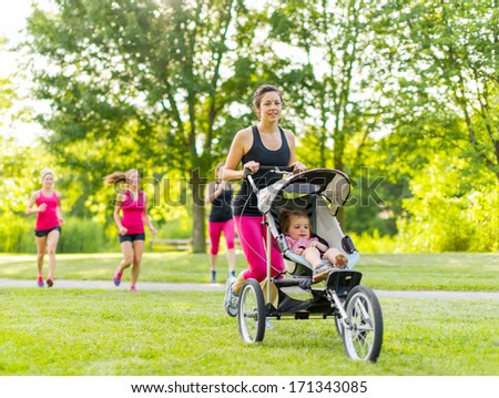 Woman pushing her little girl in a toddler while running outside with friends - stock photo