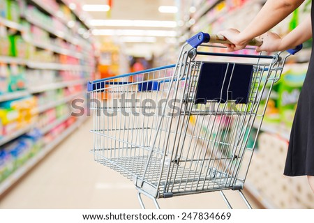 woman pushing shopping cart in supermarket - stock photo