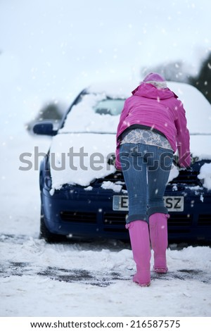 Woman pushing snow covered car in snowfall - stock photo