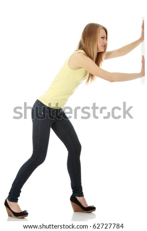 Woman pushing something imaginary isolated over a white background (white wall over her hands) - stock photo