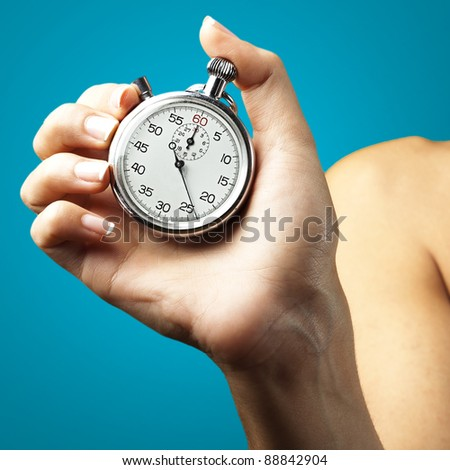 woman pushing stopwatch button against a blue background - stock photo