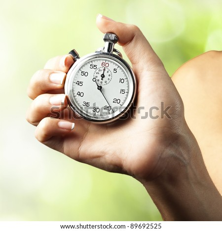woman pushing stopwatch button against a nature background - stock photo