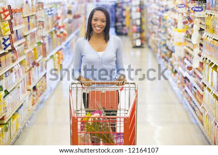 Woman pushing trolley along aisle in supermarket - stock photo