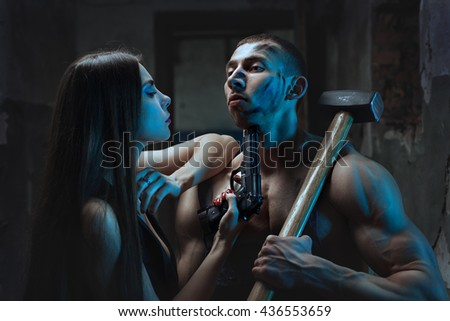 Woman put a gun to a man with big muscles. - stock photo