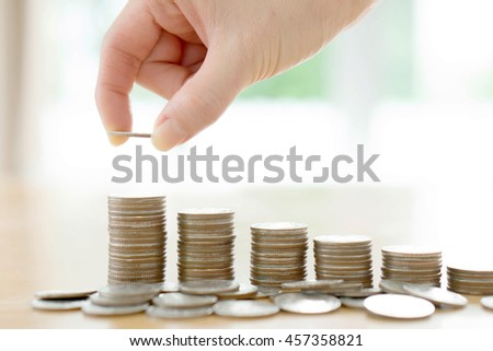 woman put coins to stack of coins