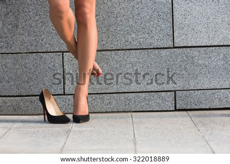 Woman put off right leg from her heel. Beautiful lady hiding right leg behinf left one isolated on brick wall backround. - stock photo