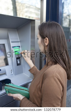 Woman puts card in ATM