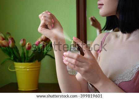 Woman puts perfume on - stock photo