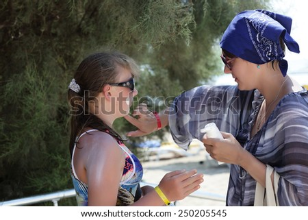 Woman puts sunscreen on girl's face at the summer resort - stock photo