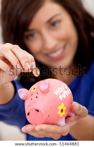 Woman putting a coin into a piggybank for the house budget - stock photo