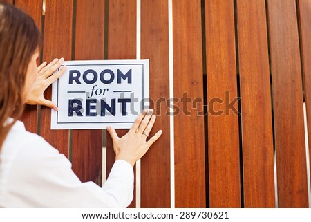 """woman putting a sight """"Room for rent on a wall"""" - stock photo"""