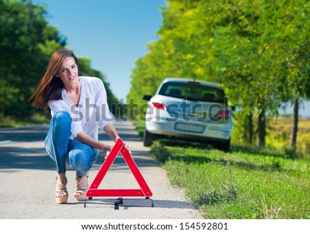 Woman putting a triangle on a road,car trouble - stock photo