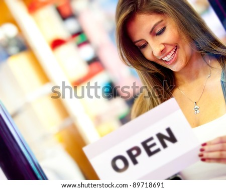 """Woman putting an """"open"""" sign at the door of a business store - stock photo"""