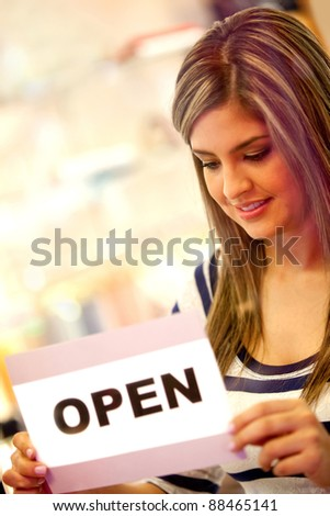 Woman putting an open sign in a retail store