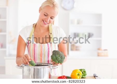 Woman putting cabbage on boiling water while wearing an apron - stock photo
