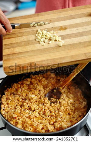 Woman putting chopped garlic in a pan with lasagna recipe on the stove - stock photo
