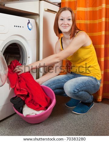 woman putting clothes into washing machine and looking at camera