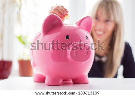 Woman putting coin in piggy bank - stock photo