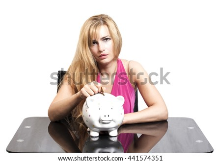 Woman putting coin in piggy bank on white background