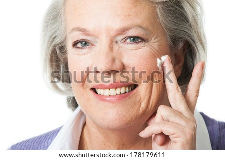 Woman putting cream on a the face - stock photo