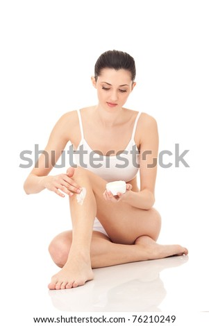 woman putting cream on her leg, isolated on background - stock photo