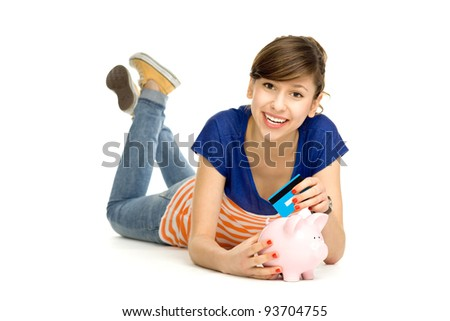 Woman putting credit card into piggy bank - stock photo