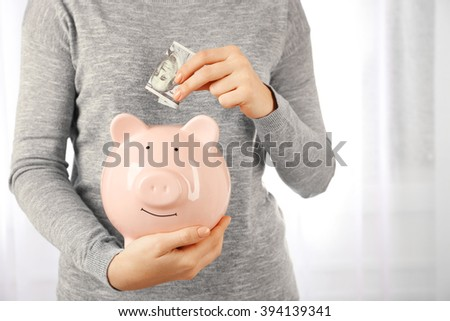 Woman putting dollar banknote into a piggy bank. Financial savings concept - stock photo