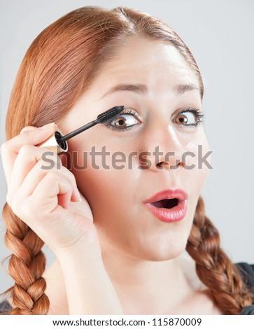 woman putting eyelash on her eyelids - stock photo