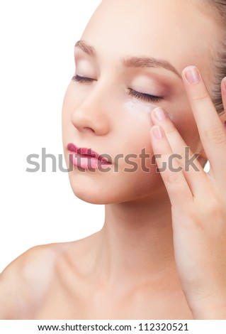 Woman putting face cream touching under eyes isolated on white background