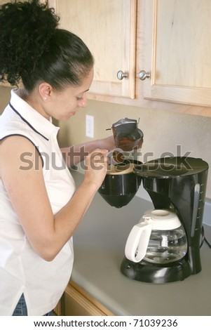 Woman putting grounds into filter in coffee machine - stock photo