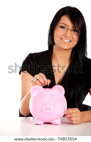 Woman putting her savings in a piggy bank ? isolated
