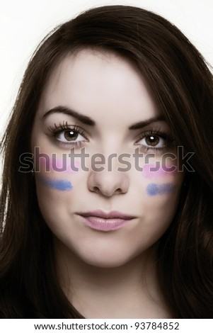 woman putting lines under her eyes as if ready for war like.  - stock photo