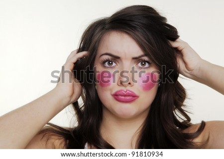 woman putting make up on and it when a bit to far so she looks silly - stock photo