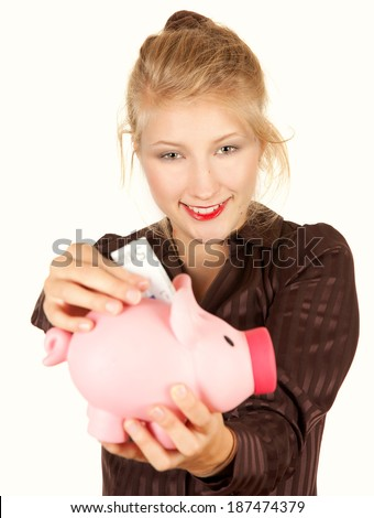 woman putting money in piggy bank, white background - stock photo