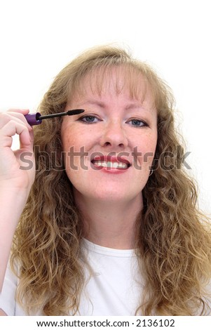 Woman putting on eye makeup. She's holding a mascara applicator. Isolated on white. - stock photo