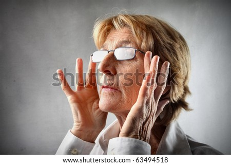 Woman putting on glasses - stock photo