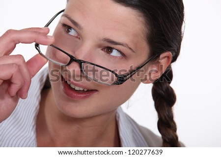woman putting on her glasses