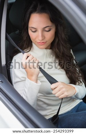 Woman putting on her seat belt in her car - stock photo