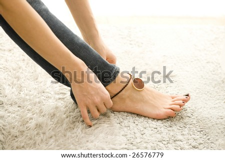woman putting on sexy anklet - stock photo