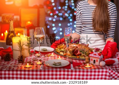 Woman putting on the Christmas decorated table turkey garnished with potato and garnet - stock photo