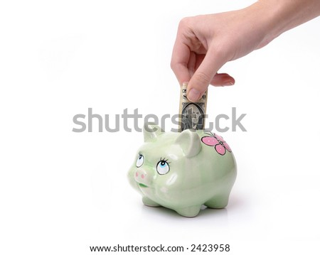 Woman putting one dollar banknote into piggybank over white background