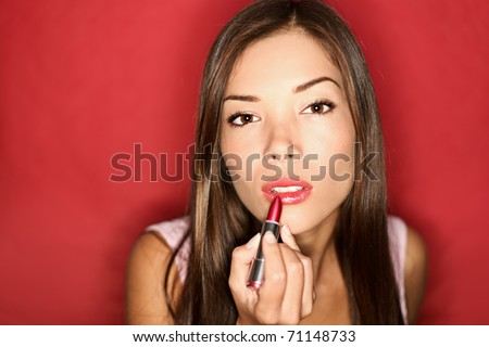 Woman putting red lipstick looking in mirror. Makeup at night getting ready before going to party. - stock photo