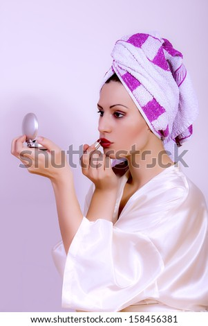 woman putting red lipstick looking in the mirror - stock photo