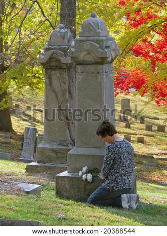 woman putting silk roses on cemetery headstone - stock photo