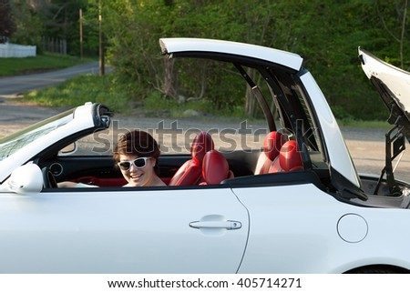 Woman Putting the Top Down on a Hardtop Convertible Sports Car